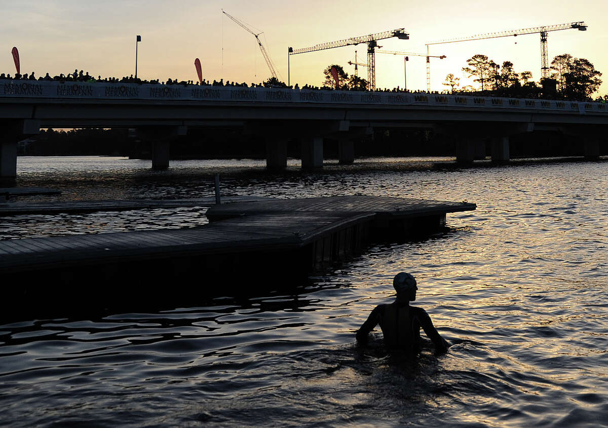 A competitor makes his way into Lake Woodlands for the swimming portion of the Ironman Texas triathlon, Saturday, May 17, 2014, in The Woodlands.