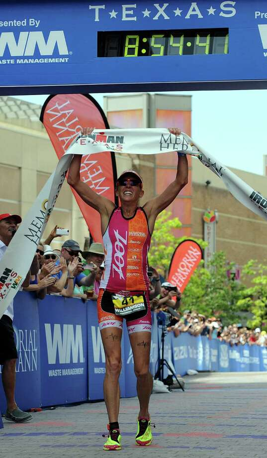 Female pro winner Kelly Williamson of Austin, TX. holds the finish line tape after winning the Ironman Texas triathlon, Saturday, May 17, 2014, in The Woodlands. Photo: Eric Christian Smith, For The Chronicle