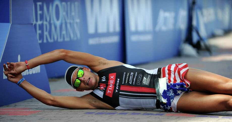 Matthew Russell of the USA rolls across the finish line for second place during the Ironman Texas triathlon, Saturday, May 17, 2014, in The Woodlands. Photo: Eric Christian Smith, For The Chronicle