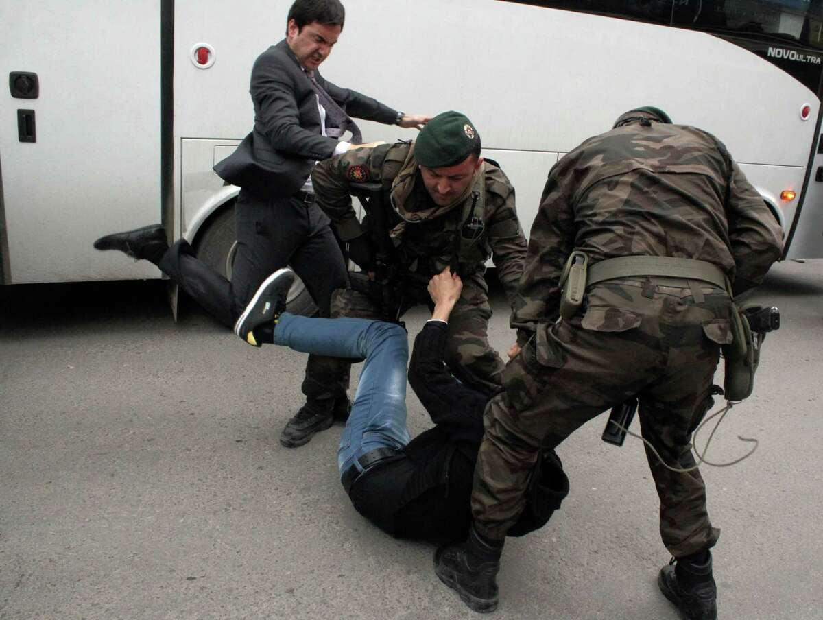 In this photo taken Wednesday, May 14, 2014 a person identified by Turkish media as Yusuf Yerkel, advisor to Turkish Prime Minister Recep Tayyip Erdogan, kicks a protester already held by special forces police members during Erdogan's visiting Soma, Turkey. Erdogan was visiting the western Turkish mining town of Soma after Turkey's worst mining accident . AP Photo/Depo Photos)