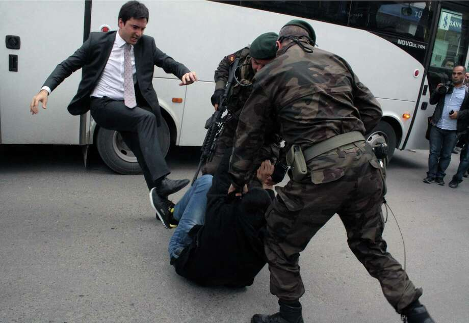 In this photo taken Wednesday, May 14, 2014  a person identified by Turkish media as Yusuf Yerkel, advisor to Turkish Prime Minister Recep Tayyip Erdogan, kicks a protester already held by special forces police members during Erdogan's visiting  Soma, Turkey. Erdogan was visiting the western Turkish mining town of Soma after Turkey's worst mining accident . AP Photo/Depo Photos)  Photo: AP  / Depo Photos