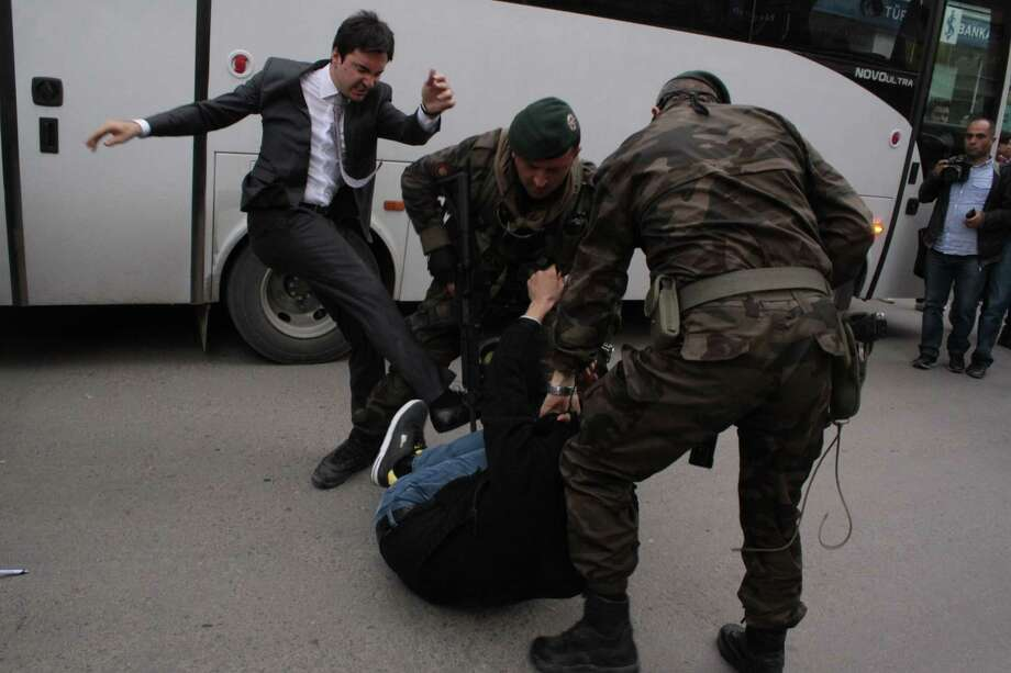 In this photo taken Wednesday, May 14, 2014  a person identified by Turkish media as Yusuf Yerkel, advisor to Turkish Prime Minister Recep Tayyip Erdogan, kicks a protester already held by special forces police members during Erdogan's visiting  Soma, Turkey. Erdogan was visiting the western Turkish mining town of Soma after Turkey's worst mining accident . AP Photo/Depo Photos)  Photo: Uncredited, AP  / AP2014