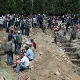 People wait for the burial ceremonies for the mine accident victims in Soma, Turkey, Thursday, May 15, 2014. An explosion and fire at a coal mine in Soma, some 250 kilometers (155 miles) south of Istanbul, killed hundreds of workers, authorities said, in one of the worst mining disasters in Turkish history.