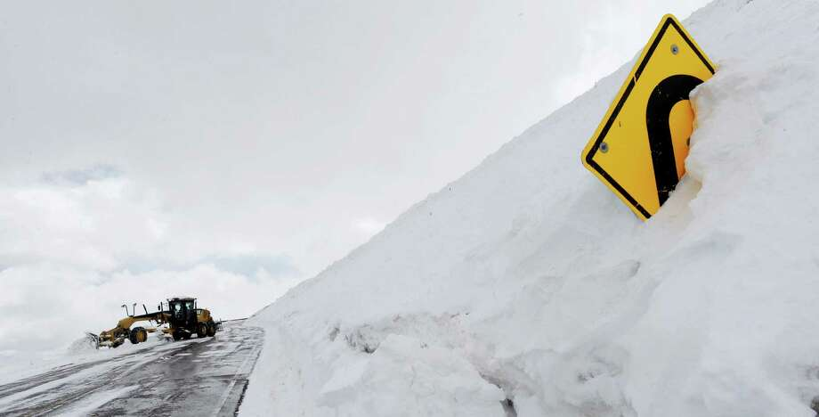 A hairpin turn road sign is nearly buried in snow along the Pikes Peak Highway on Wednesday, May 14, 2014. Since last weekend, Pikes Peak has gotten one of the biggest snowfalls of the year. About 20-24 inches have fallen in that time. Photo: JERILEE BENNETT, AP  / AP2013