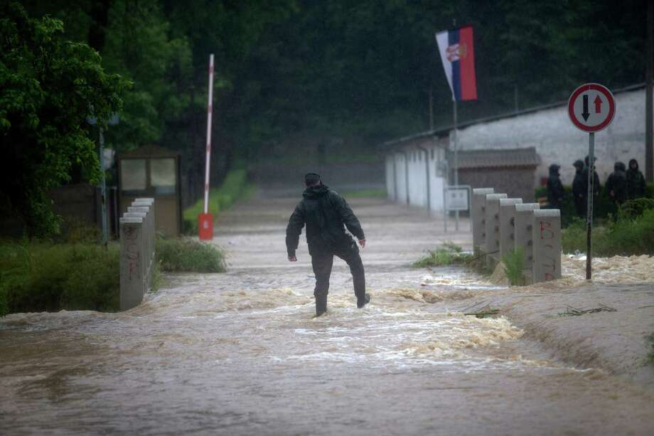 A police officer struggles as he walks along a flooded street in a suburb of Belgrade, Serbia, Thursday, May 15, 2014.  Some hundreds of people have been evacuated from their homes as floods caused by heavy rains gripped the Balkans Thursday, overflowing roads, bridges and railways, closing down schools, and cutting off power supplies and phone lines. Photo: Marko Drobnjakovic, AP  / AP2014