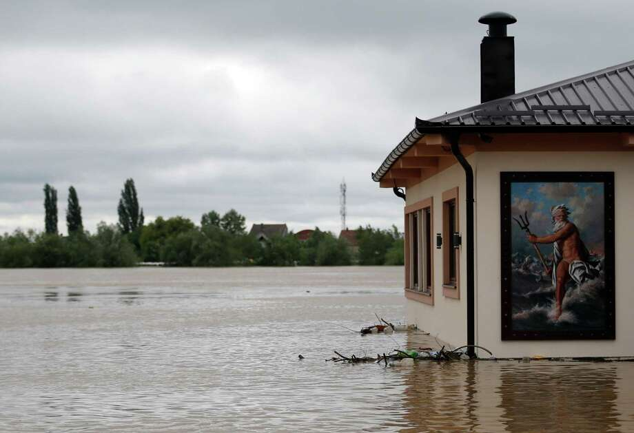"A flooded restaurant with a picture of Poseidon - ""God of the Sea"" by the bank of the Sava river in Sremska Mitrovica, 90 kilometers west of Belgrade, Serbia, Saturday, May 17, 2014. Record flooding in the Balkans leaves at least 20 people dead in Serbia and Bosnia and is forcing tens of thousands to flee their homes. Meteorologists say the flooding is the worst since records began 120 years ago. Photo: Darko Vojinovic, AP  / AP2014"