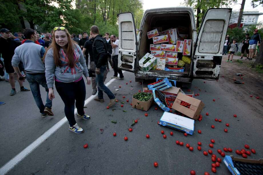 "Fruit and vegetables a strewn over the road after Russian nationalists and soccer funs attacked a truck when they decided the driver was ethnically non-Slav, during a rally to commemorate the death of a soccer fan Leonid Safyannikov, who was killed by an Uzbek on May 13 in Pushkino, about 20 kilometers from Moscow, Russia, Thursday, May 15, 2014. Later it turned out, that driver was Russian employer Denis Vasiliev, he carried vegetables to his small market. Some hundreds of people gathered near Pushkino railway station and marched through the town shouting slogans like ""Russia for Russians"" and other anti-Slav chants. Police detained about 40 activists. Photo: Pavel Golovkin, AP  / AP2014"