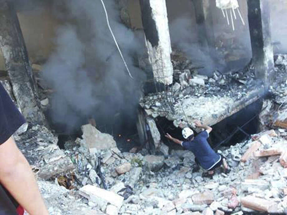 This photo provided by an anti-Bashar Assad activist group Edlib News Network (ENN), which has been authenticated based on its contents and other AP reporting, shows a Syrian man checking a damaged building at the scene where a car bomb exploded outside a mosque at Binnish town, in Idlib province, northern Syria, Friday May 16, 2014. Rebels fired a rocket that struck a government-held neighborhood Friday in the northern Syrian city of Aleppo, killing several people, Syria's state news agency reported. Photo: Anonymous, AP  / EDLIB NEWS NETWORK ENN