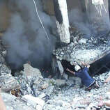 This photo provided by an anti-Bashar Assad activist group Edlib News Network (ENN), which has been authenticated based on its contents and other AP reporting, shows a Syrian man checking a damaged building at the scene where a car bomb exploded outside a mosque at Binnish town, in Idlib province, northern Syria, Friday May 16, 2014. Rebels fired a rocket that struck a government-held neighborhood Friday in the northern Syrian city of Aleppo, killing several people, Syria's state news agency reported.