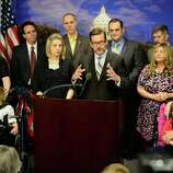 A bi-partisan group of lawmakers including Sen. Scott Dibble, center right, and Rep. Carly Melin center left, hold a news conference to present an agreement on a medical marijuana proposal that will go to a conference committee on Thursday, May 15, 2014, in St. Paul, Minn. Minnesota lawmakers struck a deal Thursday to legalize medical marijuana that would set up eight distribution sites and allow qualified patients to use the drug in oil, pill and vapor form.  (AP Photo/The Star Tribune, Glen Stubbe) Story: Minnesota lawmakers strike medical marijuana deal