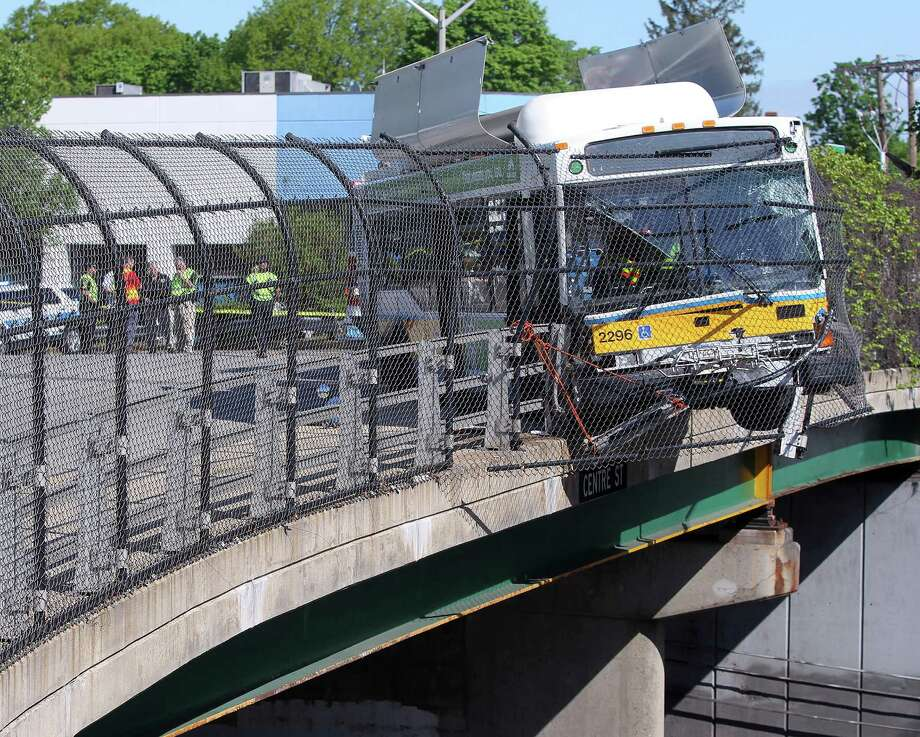 A Massachusetts Bay Transportation Authority bus hangs over the Massachusetts Turnpike after crashing on Centre Street in Newton, Mass., Sunday, May 18, 2014. Seven passengers and the bus driver were transported to a hospital with non-life-threatening injuries, MBTA spokeswoman Kelly Smith. Three other passengers declined medical treatment. Photo: Matt Stone, AP  / AP2014