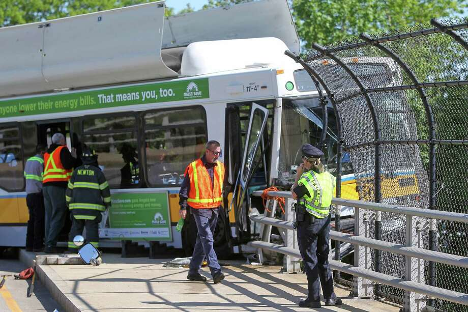 A Massachusetts Bay Transportation Authority bus hangs over the Massachusetts Turnpike after crashing on Centre Street in Newton, Mass., Sunday, May 18, 2014. Seven passengers and the bus driver were transported to a hospital with non-life-threatening injuries, MBTA spokeswoman Kelly Smith. Three other passengers declined medical treatment. Photo: Matt Stone, AP  / Boston Herald