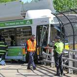 A Massachusetts Bay Transportation Authority bus hangs over the Massachusetts Turnpike after crashing on Centre Street in Newton, Mass., Sunday, May 18, 2014. Seven passengers and the bus driver were transported to a hospital with non-life-threatening injuries, MBTA spokeswoman Kelly Smith. Three other passengers declined medical treatment.