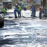 Crews sop up the remains of about 10,000 gallons of crude oil in the Atwater Village section of Los Angeles on Thursday, May 15, 2014. A geyser of crude spewed 20 feet high over approximately half mile into Los Angeles streets and onto buildings early Thursday after a high-pressure pipe burst.