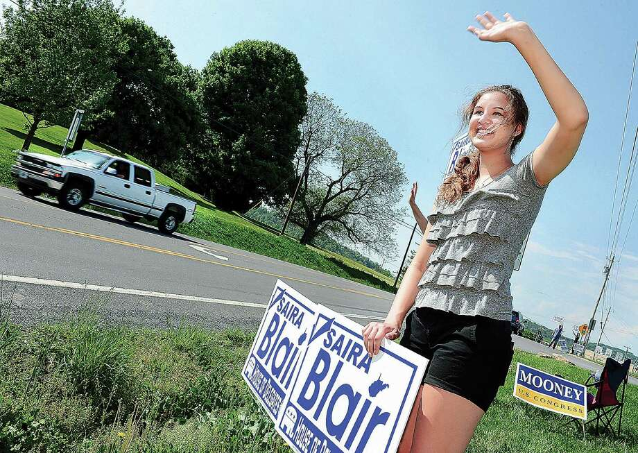 In this May 13, 2014 photo, Saira Blair, a 17-year-old student at Hedgesville High School, waves to motorists along Route 9 in Hedgesville, W. Va. After Tuesday's GOP primary, the 17-year-old is one election away from becoming the youngest state lawmaker in West Virginia history. Photo: Ric Dugan, AP  / AP2014