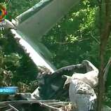 This image taken from video provided by Lao National TV, shows the wreckage of a Lao air force plane which crashed in a forested area of Xiangkhoung province, Laos Saturday, May 17, 2014. The Lao air force plane carrying senior government officials crashed Saturday, killing at least five people on board, including the country's Defense Minister Douangchay Phichit, Thai officials said. (AP Photo/Lao National TV via AP Video)
