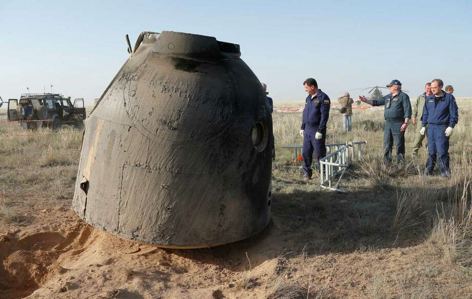 A rescue team arrives as the Russian Soyuz TMA-11M space capsule stands on the ground shortly after landing, some 150 kilometers (93 miles) southeast of town Dzhezkazgan, Kazakhstan, Wednesday, May 14, 2014. The Soyuz space capsule with Japanese astronaut Koichi Wakata, Russian cosmonaut Mikhail Tyurin and U.S. astronaut Rick Mastracchio, returning from a half-year mission to the International Space Station, landed safely Wednesday on the steppes of Kazakhstan. Photo: Dmitry Lovetsky, AP  / AP POOL