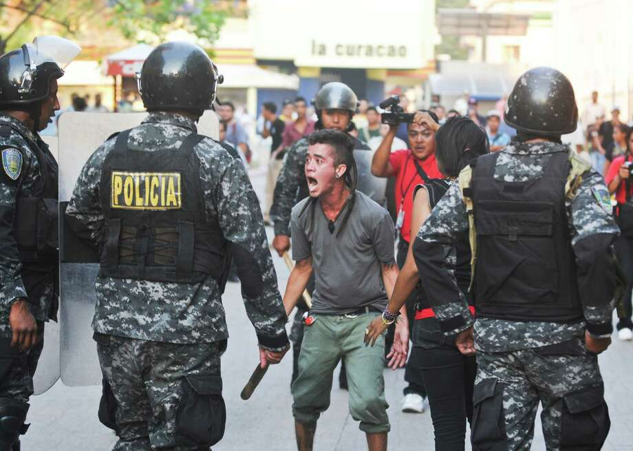 Supporters of the Libertad y Refundacion, LIBRE, political party, shout slogans against the Honduran government during a clashes with police, outside the congress building in Tegucigalpa, Honduras, Tuesday, May 13, 2014. Hundreds of supporters of former President and now Congressman, Manuel Zelaya, clashed with riot police and soldiers after occupying the National Congress building with him. They where eventually expelled violently from the building. Photo: Fernando Antonio, AP  / AP
