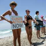 Claudia Reyna of Miami, left, joins hands with a line of activists and beachgoers participating in  Hands across the Sand, part of simultaneous events happening globally to raise awareness of the need to end our dependence on fossil fuels and transition to clean energy.