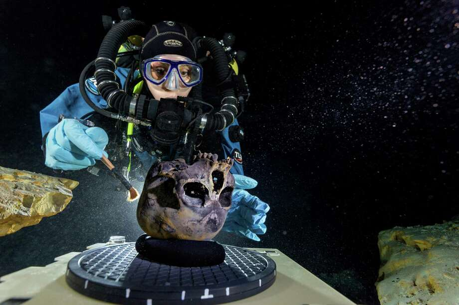 In this June 2013 photo provided by National Geographic, diver Susan Bird, working at the bottom of Hoyo Negro, a large dome-shaped underwater cave in Mexico's Yucatan Peninsula, brushes a human skull found at the site while her team members take detailed photographs. Thousands of years ago, a teenage girl fell into this deep hole and died. Now, her skeleton and her DNA are helping scientists study the origins of the first Americans. An analysis of her remains was released Thursday, May 15, 2014 by the journal Science. Her DNA links her to an ancient land bridge connecting Asia and North America, and suggests she shares ancestors with the modern native peoples of the Americas. Photo: Paul Nicklen, AP  / PAUL NICKLEN2013