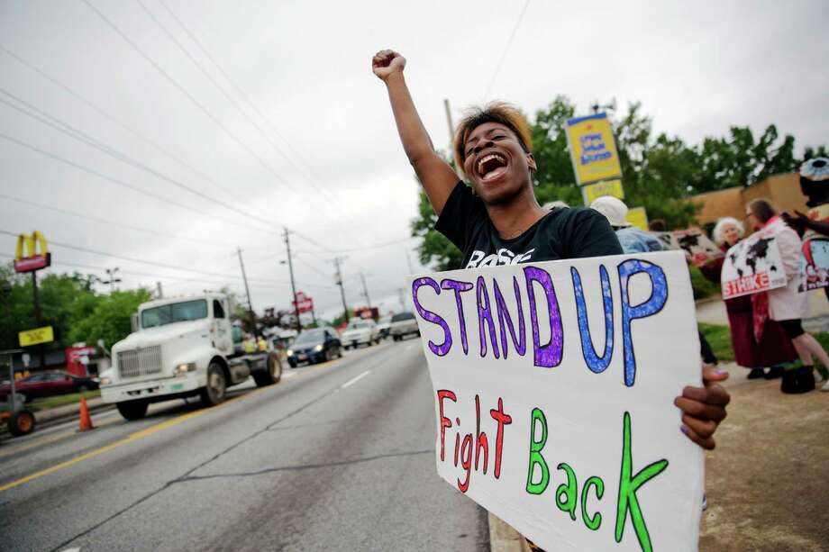 Carmen Burley-Rawls, 20, shouts to passing motorists during a protest outside a Long John Silver's and McDonald's restaurant, Thursday, May 15, 2014, in Atlanta. Calling for higher pay and the right to form a union without retaliation, fast-food chain workers in Atlanta protested Thursday as part of a wave of strikes and protests in 150 cities across the U.S. and 33 additional countries on six continents. Photo: David Goldman, AP  / AP2014