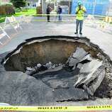 In this photo taken on Monday, May 12, 2014, a person takes a photo of a large sink hole that opened up on Carlin St., North of Tireman in Detroit. (AP Photo/Detroit News,  Daniel Mears )