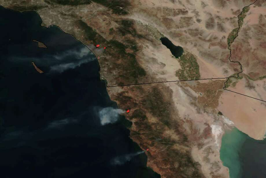 This May 14, 2014 image provided by NASA shows numerous large wildfires burning across sections of northern Baja and southern California, producing plumes of moderate to dense smoke and combining with blowing dust and sand moving west off the coast and well into the Pacific Ocean. Nine fires in all were burning an area of more than 14 square miles amid a heat wave and dry conditions, said San Diego County officials, who warned also of poor air quality with black and gray smoke wafting over the region. Photo: NASA, AP  / AP2014