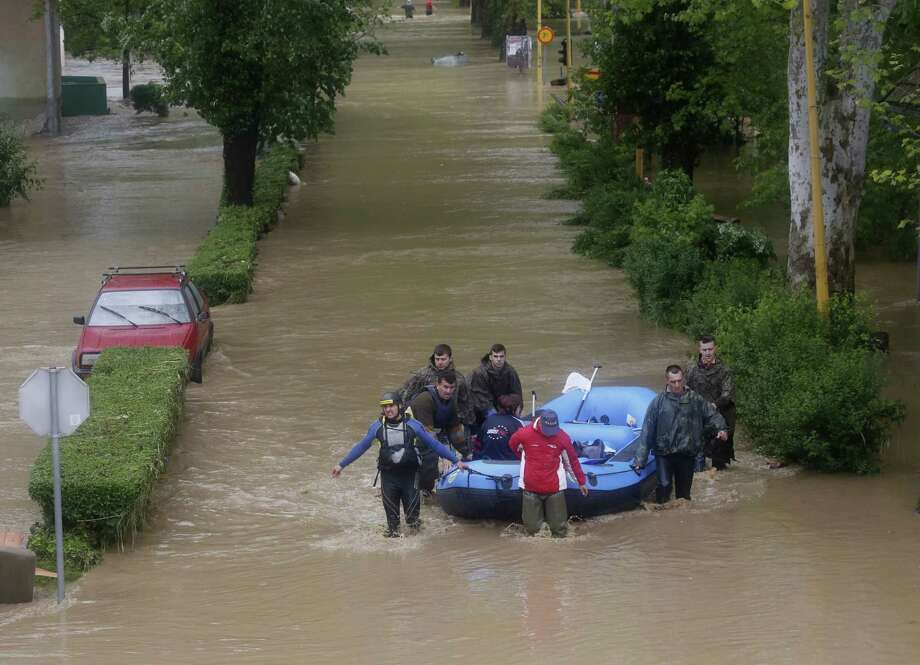 Members of the Bosnian Army rescue people from their flooded homes,  in the Bosnian town of Maglaj, 150 kms north of Sarajevo, Friday May 16, 2014. Two people drowned in Serbia and the country declared a national emergency Thursday as rain-swollen rivers across the Balkans flooded roads and bridges, shut down schools and cut off power. Hundreds of people had to be evacuated. In Serbia and neighboring Bosnia, meteorologists said the rainfall was the most since measuring started 120 years ago. Belgrade authorities say the average rainfall of a two-month period hit the city in just 40 hours. Photo: Amel Emric, AP  / AP