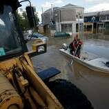 People paddle a boat through a flooded street in Obrenovac, some 30 kilometers (18 miles) southwest of Belgrade, Serbia, Sunday, May 18, 2014. Floodwaters triggered more than 2,000 landslides across much of the Balkans on Sunday, laying waste to entire towns and villages and disturbing land mines left over from the region's 1990s war, along with warning signs that marked the unexploded devices.