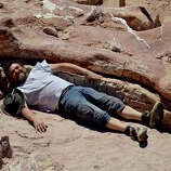 In this January 2014 photo released on Saturday, May 17, 2014 by the Museo Paletontol-gico Egidio Feruglio, Spanish paleontologist Jose Ignacio Canudo lies alongside a sauropod dinosaur femur, believed to be the largest in the world, in Trelew, Argentina. Paleontologists from the Museo Paletontol-gico Egidio Feruglio, announced Friday, May 16, 201, the discovery of the fossil remains of the sauropod dinosaur near Trelew.