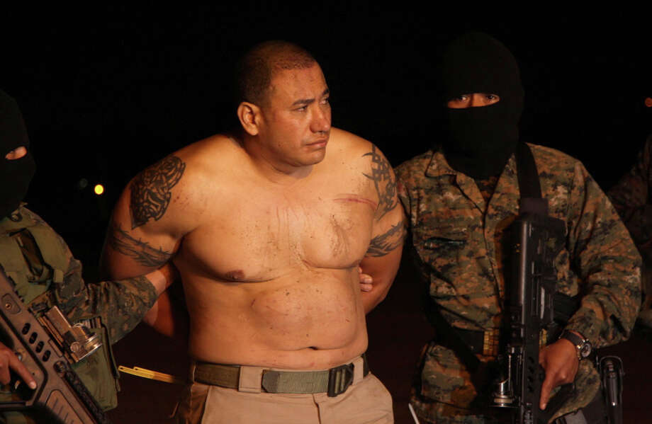 In this photo released by the National Civil Police, masked soldiers escort Jairo Estuardo Orellana in handcuffs after his arrest as they bring him to an air force base in Guatemala City, late Thursday, May 15, 2014. Guatemala's Interior Minister Mauricio Lopez Bonilla announced the government detained Orellana, an alleged member of Mexico's Zetas Cartel drug gang who is described by the U.S. government as one of the region's most important drug traffickers, during an operation in which two of Orellana's bodyguards we killed, as well as a police officer, in town of Gualan in the Zacapa department. Photo: AP  / National Civil Police
