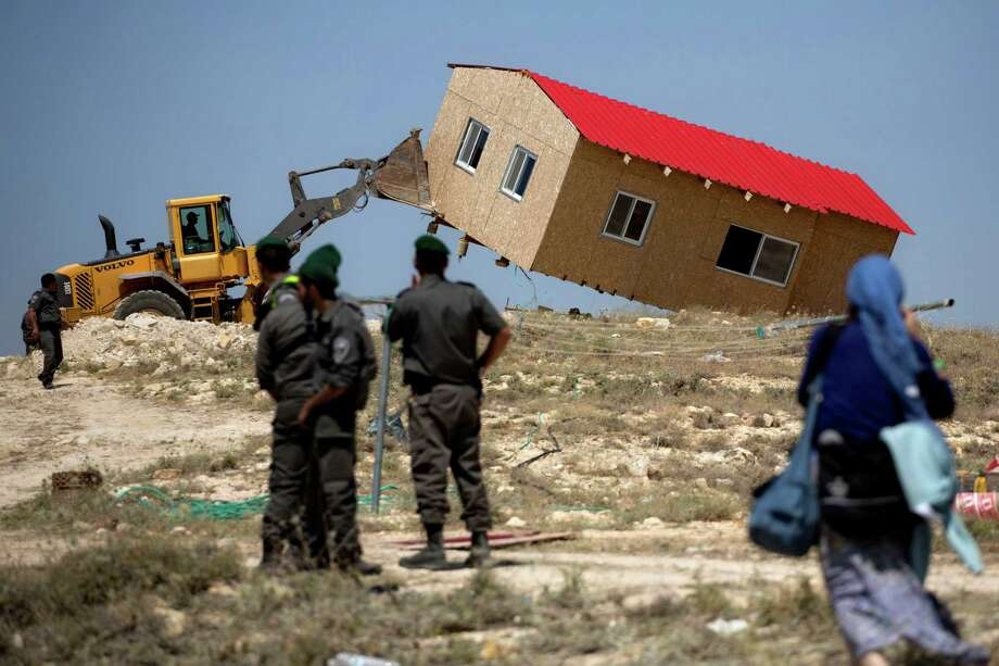 Israeli border police officers stand guard as a house is demolished in the Wesk Bank Jewish settlement of Maaleh Rehavam, Wednesday, May 14, 2014. Israel's Supreme Court ruled that the land the houses were built on belong to Palestinians. Photo: Sebastian Scheiner, AP  / THE ASSOCIATED PRESS2014