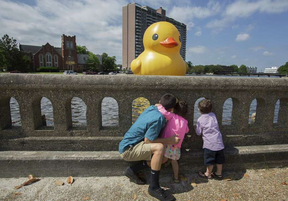 "Alonzo Lapitan,15, with his sister and brother, Aniston and Anderson, both 2, of Virginia Beach get a look at the 40- foot ""Rubber Duck"" in the Hague inlet by artist Florentijn Hofman  at the Chrysler Museum of Art in Norfolk, Va, on Saturday, May 17, 2014. Photo: Bill Tiernan, AP  / The Virginian-Pilot"
