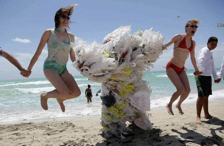 Rachel Bennett, of Brooklyn, N.Y., left, and Tiffany Threadgould, of Philadelphia, Pa., right, leap into the air as a friend takes their photograph, while joining hands with Steve Vincenti of Miami, center, who is covered with plastic shopping bags, during the Hands across the Sand protest, Saturday, May 17, 2014 photo, in Miami Beach, Fla. The protest is part of simultaneous events happening globally to raise awareness of the need to end our dependence on fossil fuels and transition to clean energy. Photo: Lynne Sladky, AP  / AP