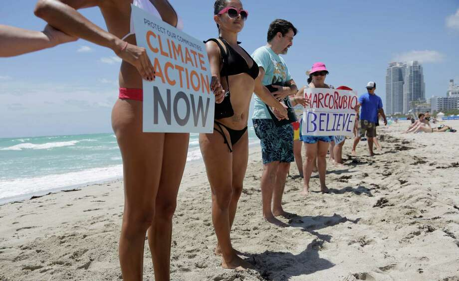 Claudia Reyna of Miami, left, joins hands with a line of activists and beachgoers participating in  Hands across the Sand, part of simultaneous events happening globally to raise awareness of the need to end our dependence on fossil fuels and transition to clean energy. Photo: Lynne Sladky, AP  / AP