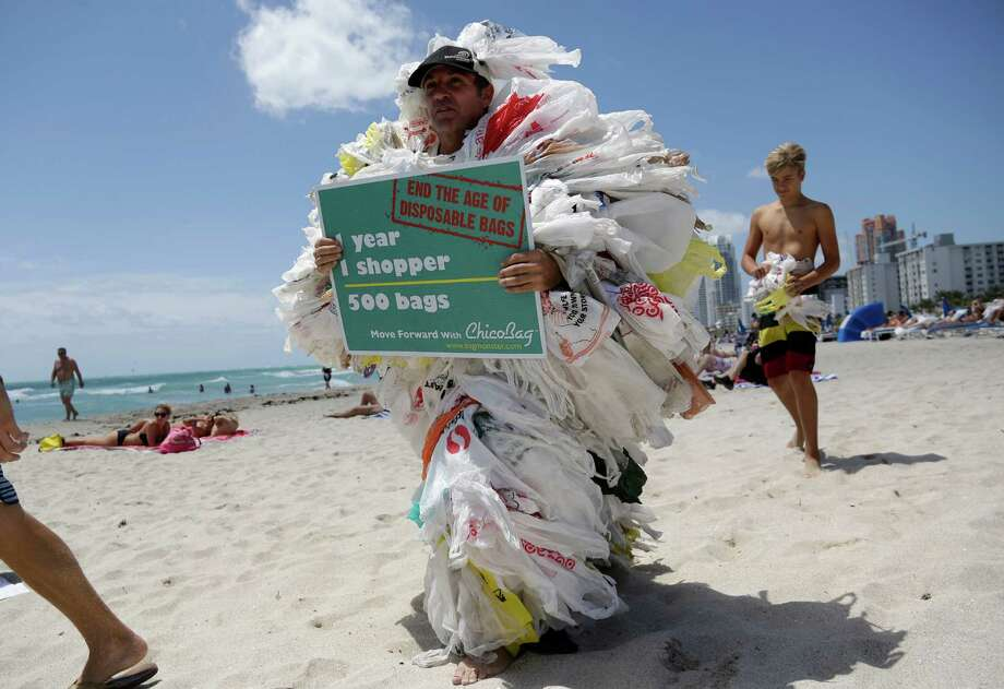 Steve Vincenti of Miami walks on the beach wearing 500 plastic shopping bags, protesting the use of disposable bags, during a Hands across the Sand event, part of simultaneous events happening globally to raise awareness of the need to end our dependence on fossil fuels and transition to clean energy. Photo: Lynne Sladky, AP  / AP2014