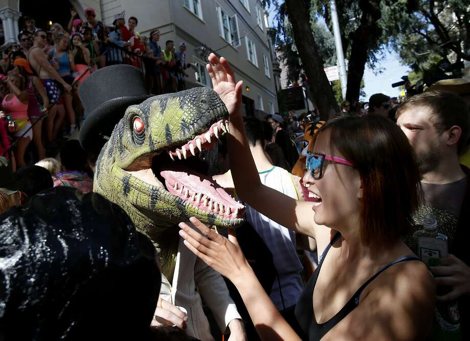 A woman tried to deal with a prehistoric runner in front of a large party of Hayes Street. The annual Bay to Breakers event in San Francisco, Calif.  attracted thousands of runners and revelers as they made their way up the Hayes Street Hill Sunday May 18, 2014. Photo: Brant Ward, The Chronicle