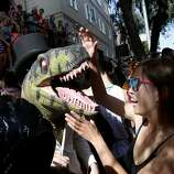 A woman tried to deal with a prehistoric runner in front of a large party of Hayes Street. The annual Bay to Breakers event in San Francisco, Calif.  attracted thousands of runners and revelers as they made their way up the Hayes Street Hill Sunday May 18, 2014.