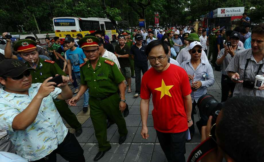Police ask people to leave a street near the Chinese Embassy in Hanoi as heavy security clamps down on protests. Photo: Hoang Dinh Nam, AFP/Getty Images