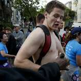 A man had his bottle of champagne grabbed by a security officer. The annual Bay to Breakers event in San Francisco, Calif. attracted thousands of runners and revelers as they made their way up the Hayes Street Hill Sunday May 18, 2014.