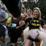 Bat woman got friendly with a security guard. The annual Bay to Breakers event in San Francisco, Calif. attracted thousands of runners and revelers as they made their way up the Hayes Street Hill Sunday May 18, 2014.