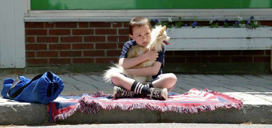 Ciaran Vizi, 9, of Bethel, and Nala hold a spot along the curb of Greenwood Avenue before the start of the Annual Memorial Day Parade in Bethel, Conn, on Sunday afternoon, May 18, 2014. The parade of marching bands, military vehicles, sports teams, scouts, veterans and more went down Greenwood Ave. and ended at the front of the Hurgin Municipal Center. Photo: H John Voorhees III / The News-Times Freelance