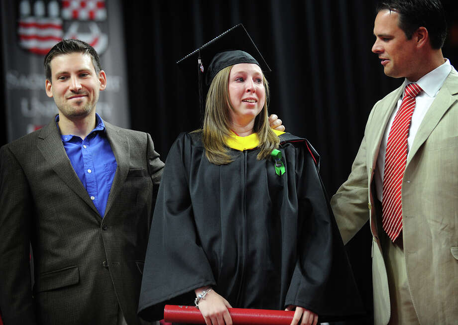 Sacred Heart graduate Alison Cubbellotti, of Trumbull, her organ donor, fellow SHU grad John Vales, left, of Somers, NY, and Cubbellotti's godfather Jorge Rivera, of Fairfield, react to a standing ovation after she received her diploma at the Webster Bank Arena in Bridgeport, Conn. on Sunday, May 18, 2014. Vales donated sixty percent of his liver in 2009 to provide fellow student Cubbellotti with a life saving liver transplant. Photo: Brian A. Pounds / Connecticut Post