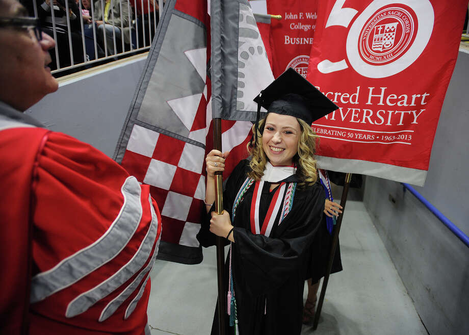 Graduate Kelsey Russo, of Middletown, carries the university flag in procession during the Sacred Heart University graduation at the Webster Bank Arena in Bridgeport, Conn. on Sunday, May 18, 2014. Photo: Brian A. Pounds / Connecticut Post