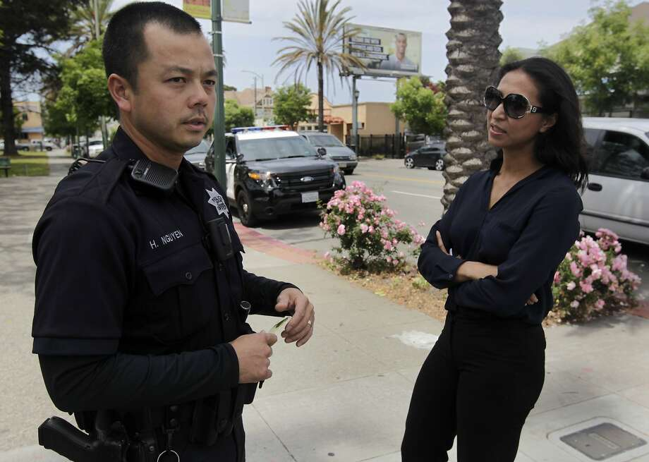 Oakland police Officer Huy Nguyen meets with local businesswoman Thu Pham, who says police have become more responsive to concerns in the Eastlake neighborhood in the past year. Photo: Paul Chinn, The Chronicle