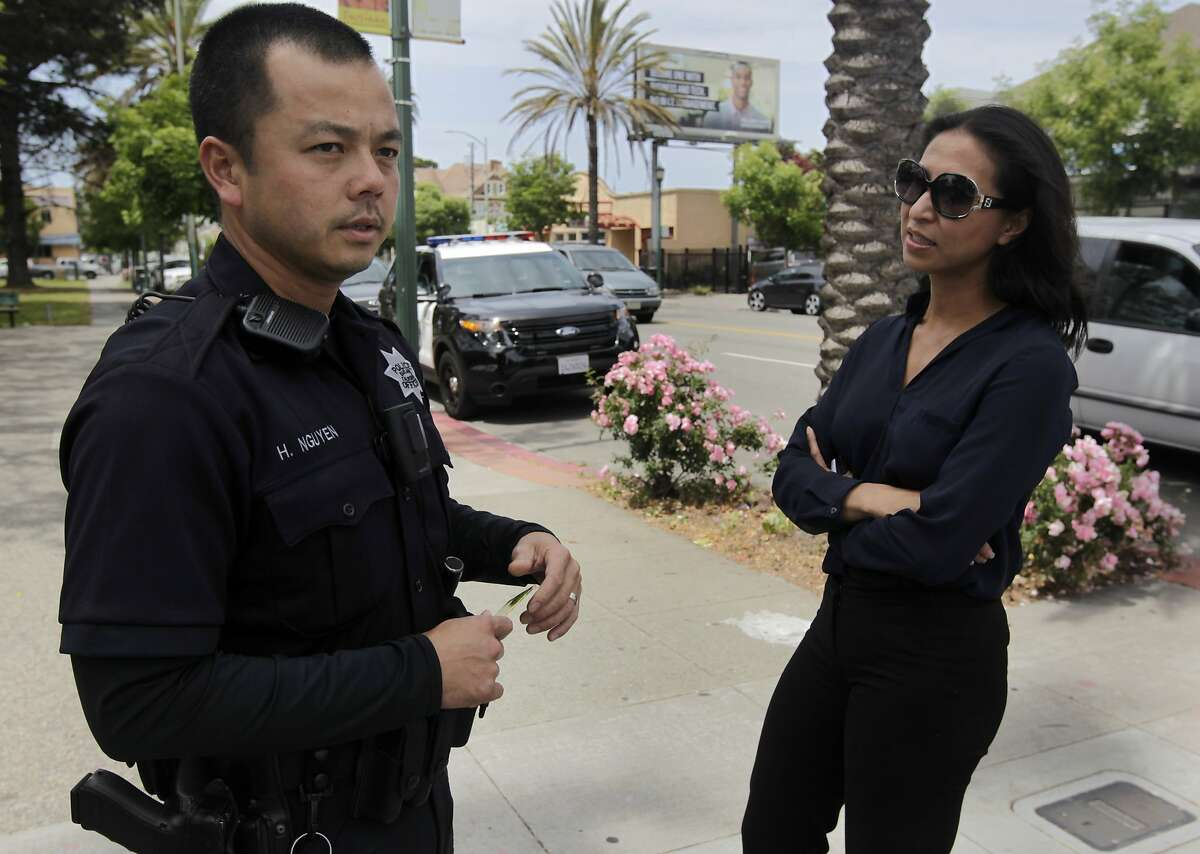 Oakland police officer Huy Nguyen meets with local businesswoman Thu Pham in the Eastlake neighborhood of Oakland, Calif. on Saturday, May 17, 2014. The crime rate has dropped significantly in the neighborhood and citywide as a whole in the past year.