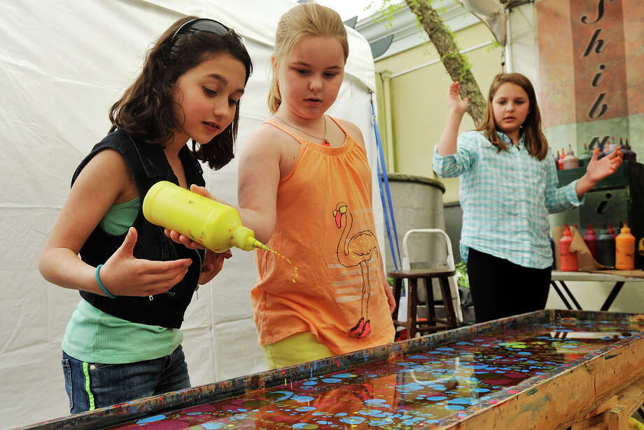 Isabella Robertson, left, and her sister, Sophie, right, watch as their friend, Deirdre Cunniffe, drops paint on water in a design that will transfer to a silk scarf at the Shibumi Silks exhibitor tent during the 29th annual Outdoor Crafts Festival at the Bruce Museum in Greenwich, Conn., on Sunday, May 18, 2014. The process of creating the design on fabrics is known as the ancient art of water marbling. Photo: Jason Rearick / Stamford Advocate