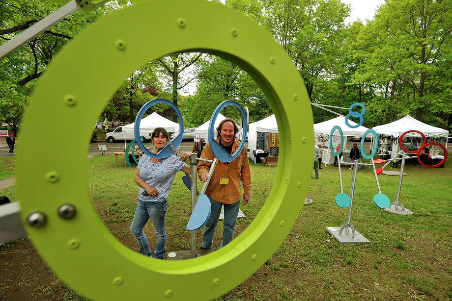 Audrey and Drew Klotz pose among Drew's sculptures during the 29th annual Outdoor Crafts Festival at the Bruce Museum in Greenwich, Conn., on Sunday, May 18, 2014. Drew's sculptures will also be on display from 2-4 p.m. at the UConn Stamford art gallery on June 7. Photo: Jason Rearick / Stamford Advocate