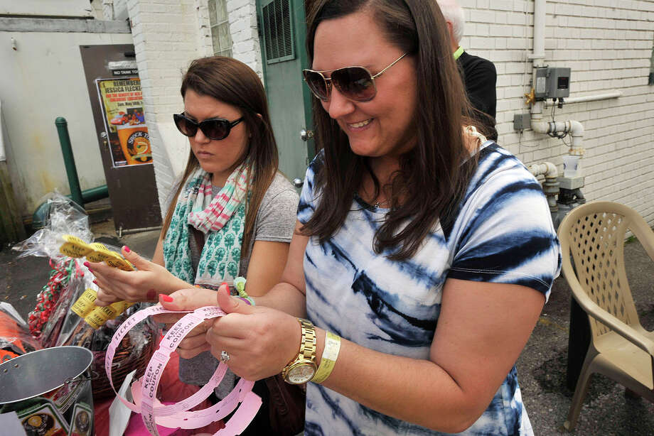 Allison Alter, left, and Kayla Romaniello sell raffle tickets during a benefit event for Stamford native Jessica Fleckenstein, 35, who died of a brain aneurism, at Fiddler's Green in Stamford, Conn., on Sunday, May 18, 2014. The benefit was to raise money for Jessica's children to go to college. To make a donation, send cash or make a check out to cash in care of Tom Richter at Fiddler's Green. Romaniello is Jessica's cousin. Photo: Jason Rearick / Stamford Advocate