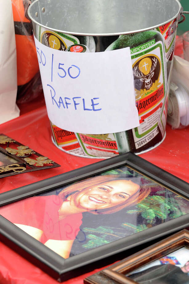 A portrait of Stamford native Jessica Fleckenstein is displayed next to the 50/50 raffle bucket during a benefit event for Fleckenstein, 35, who died of a brain aneurism, at Fiddler's Green in Stamford, Conn., on Sunday, May 18, 2014. The benefit was to raise money for Jessica's children to go to college. To make a donation, send cash or make a check out to cash in care of Tom Richter at Fiddler's Green. Photo: Jason Rearick / Stamford Advocate